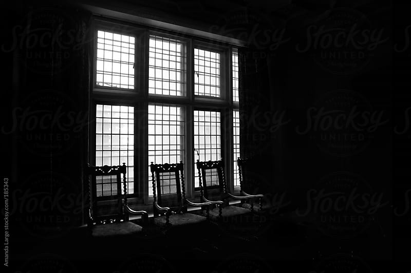 silhouette of chairs against a window in a dark room by Amanda Large for Stocksy United