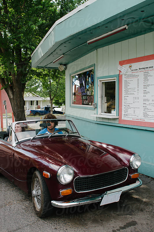 couple sitting in convertible waiting for food a drive thru restaurant