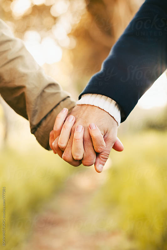 Closeup of anonymous couple holding hands in the forest. by BONNINSTUDIO for Stocksy United