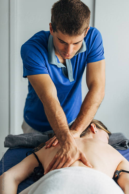 Long view of a woman's body lying on her front whilst receiving a massage on her lower back from a young male physiotherapist by Inuk Studio for Stocksy United