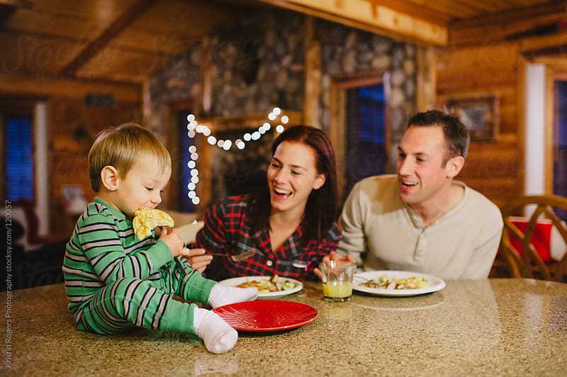 Mother and Father laughing a toddler son bring silly with food by Kristin Rogers Photography for Stocksy United