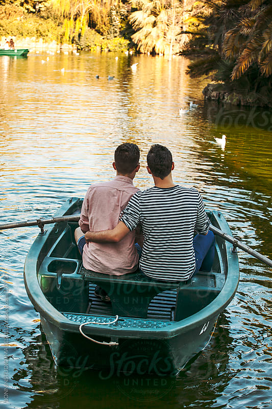 Back view of gay couple rowing boat on a lake. by BONNINSTUDIO for Stocksy United
