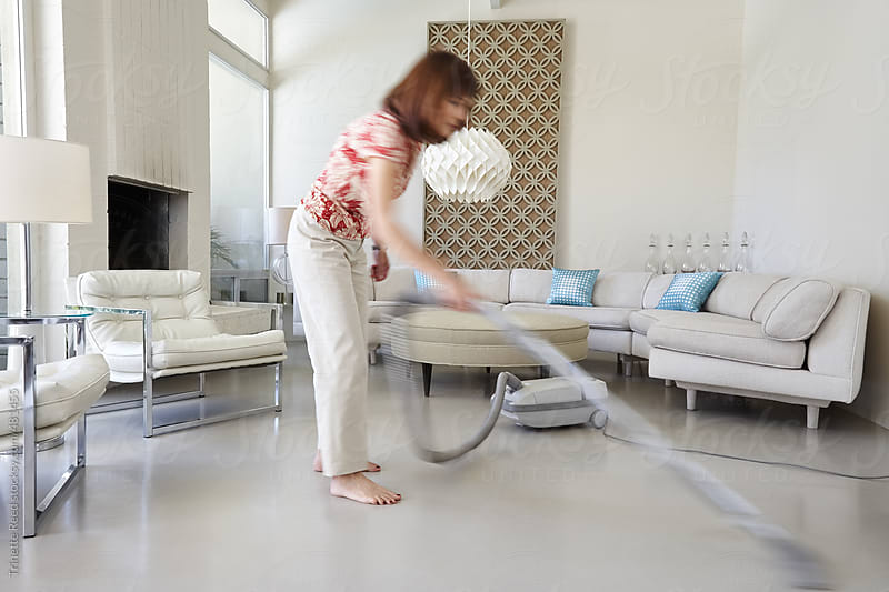 Mature woman cleaning her modern design home by Trinette Reed for Stocksy United