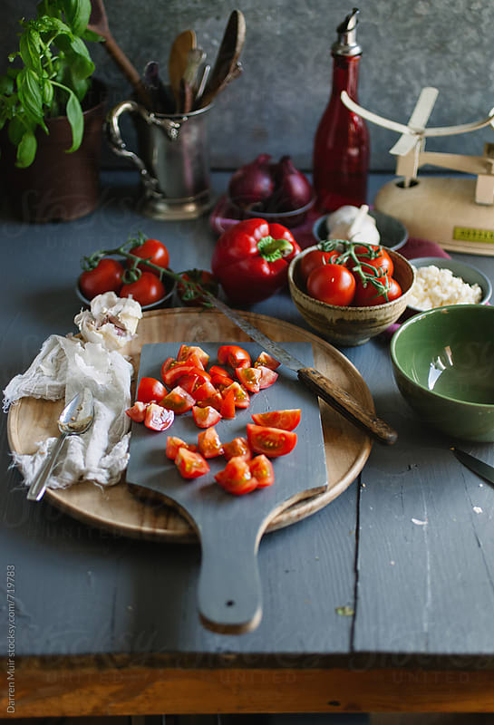 Chopped tomatoes on a cutting board surrounded by other vegetables,on a table. by Darren Muir for Stocksy United