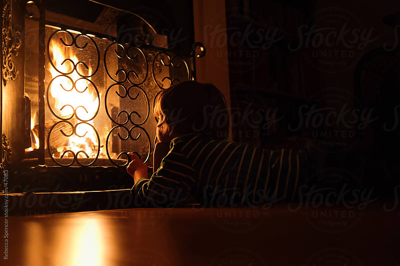 Boy watching indoor fire by Rebecca Spencer for Stocksy United
