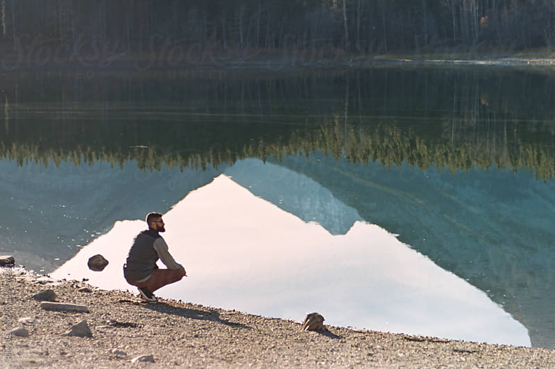 A bearded man crouched at the bank of a mountain pond by Riley J.B. for Stocksy United