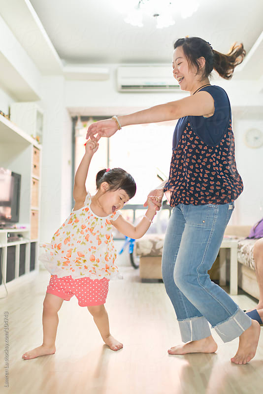 girl dancing with mother at home by Lawren Lu for Stocksy United