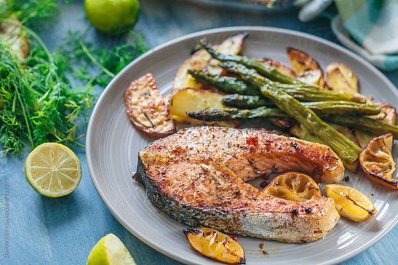 Roasted salmon with asparagus and potatoes by Davide Illini for Stocksy United