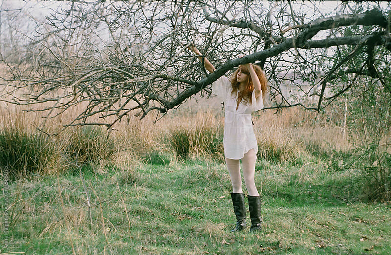 A film portrait of a young beautiful redhead woman touching the tree in russian countriside by Anna Malgina for Stocksy United
