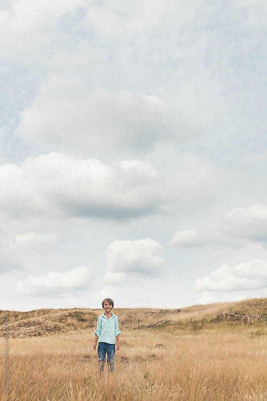 Little boy standing alone in a field underneath a big cloudy sky by Cindy Prins for Stocksy United