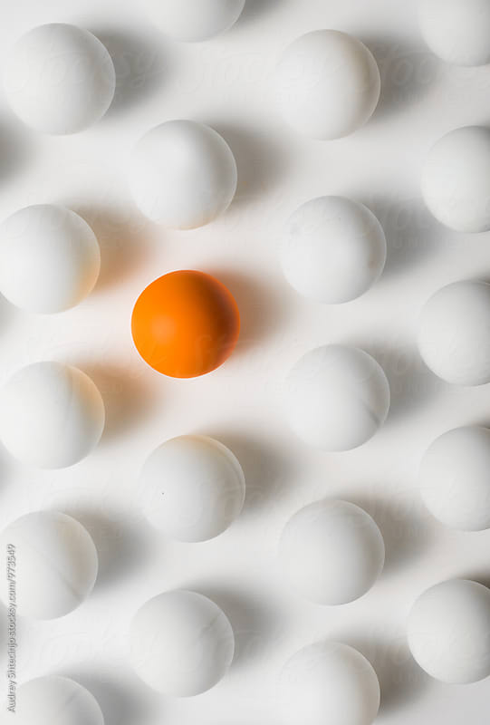 Orange ping pong balls surrounded with white balls one white background . by Audrey Shtecinjo for Stocksy United