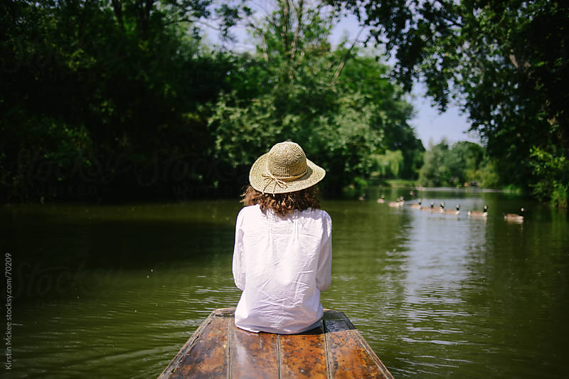 Girl sitting on the front of a punt in Oxford by Kirstin Mckee for Stocksy United