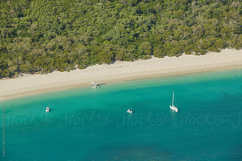 Boats and a Seaplane moored in Whitehaven Beach by Joaquim Bel for Stocksy United