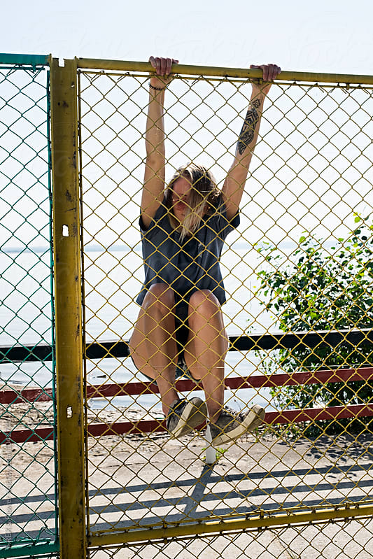 Blonde wild girl with tattoo climbing the fence by Danil Nevsky for Stocksy United