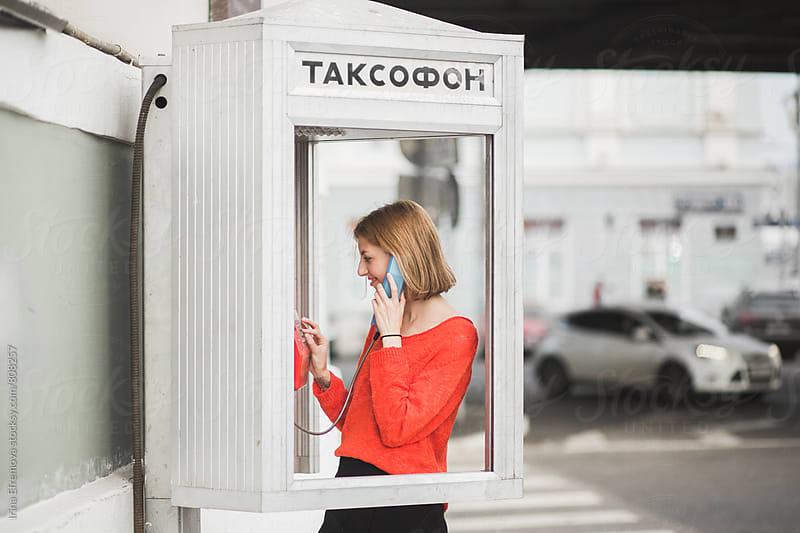 Girl in a telephone booth by Irina Efremova for Stocksy United