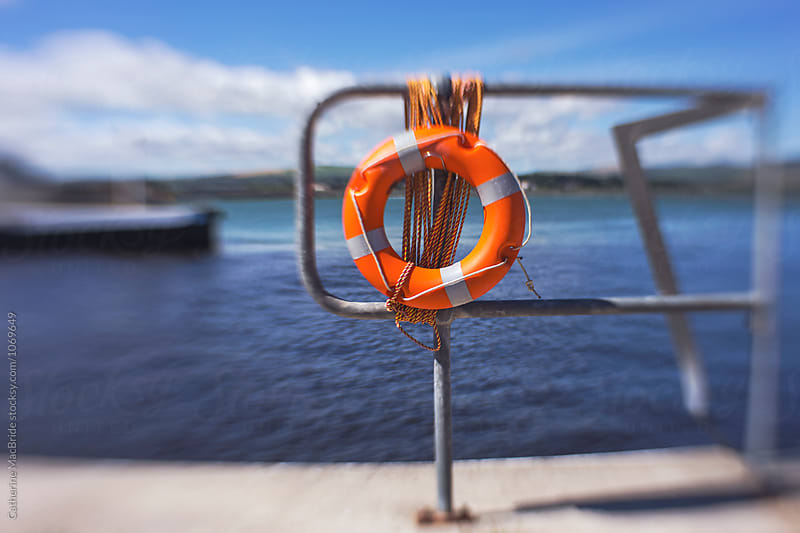 Life Bouy on harbour railing... by Catherine MacBride for Stocksy United