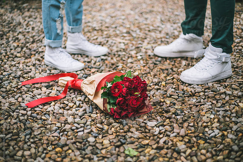 Couple and Valentine's gift - bouquet of red roses on the floor. Close up. by Jovo Jovanovic for Stocksy United