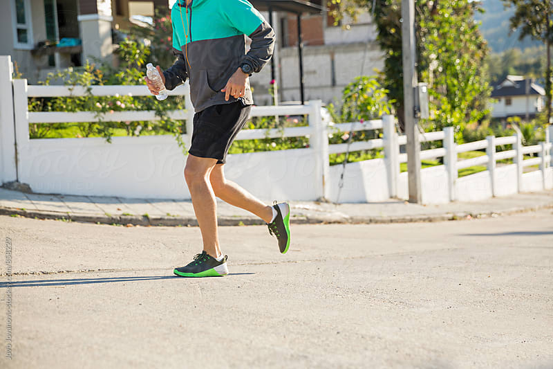 Closeup of an athletic healthy man running uphill in the street  by Jovo Jovanovic for Stocksy United