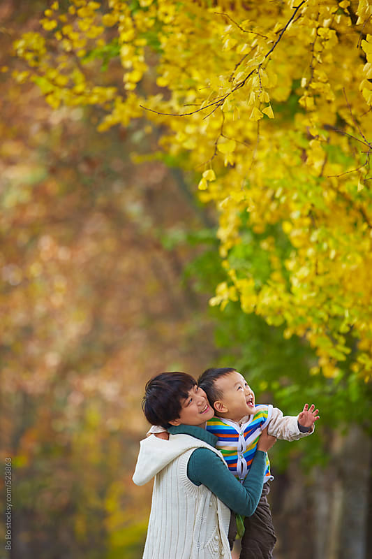 happy asian mother with her son in autumn woods by Bo Bo for Stocksy United