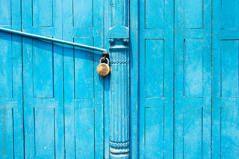 Padlock on a blue door by Bisual Studio for Stocksy United