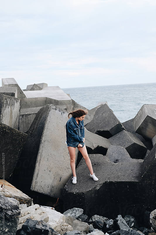 A beautiful young girl stands on a sea wall in Wellington by Maximilian Guy McNair MacEwan for Stocksy United