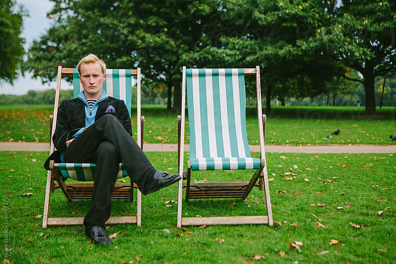 Young man sitting in a park next to an empty chair by kkgas for Stocksy United