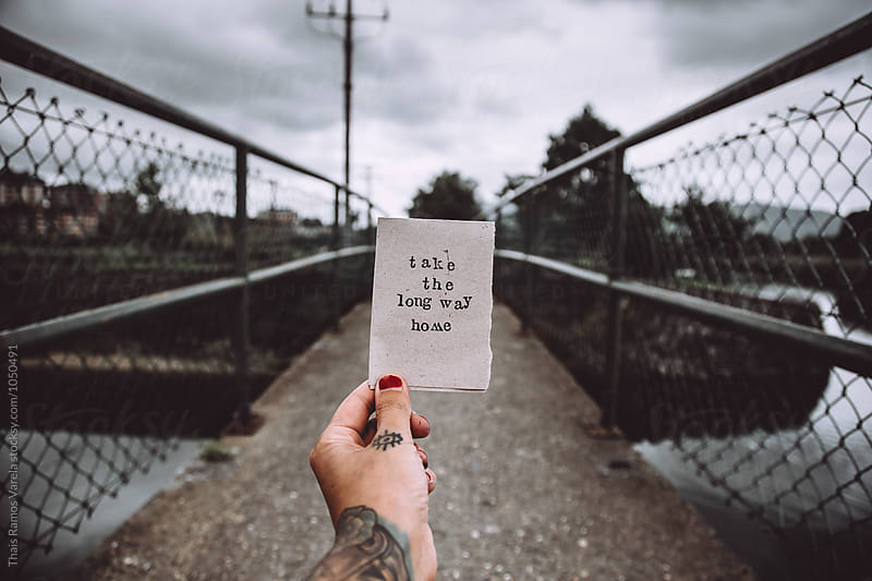 hand hoding a message behind a river bridge by Thais Ramos Varela for Stocksy United
