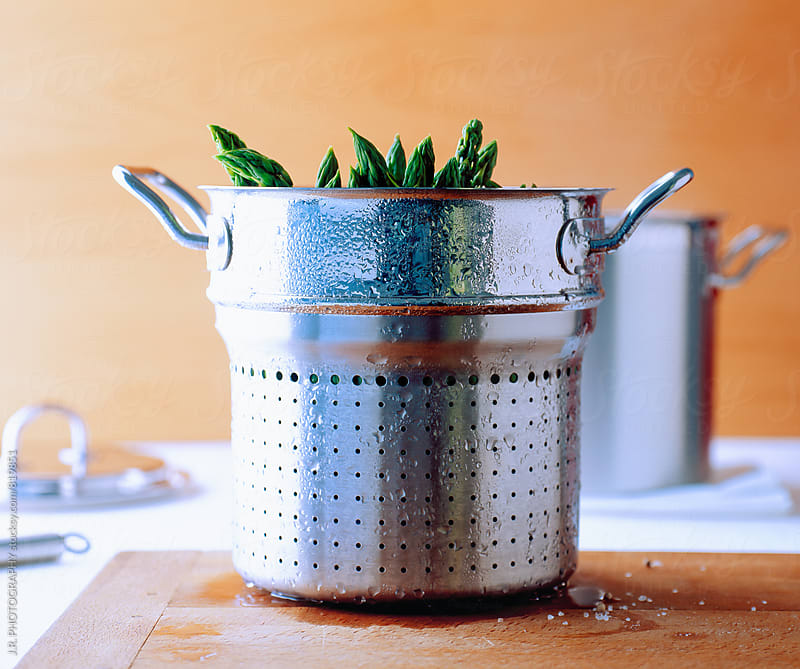 Pot with asparagus in steamer basket by J.R. PHOTOGRAPHY for Stocksy United