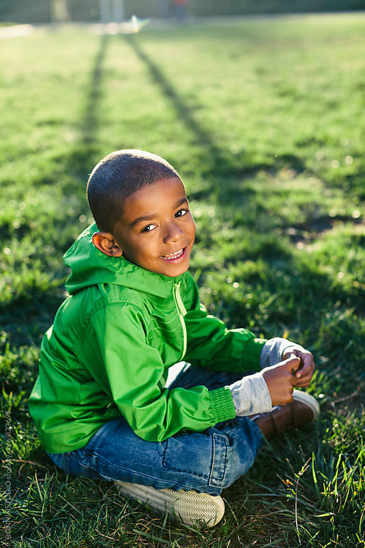 Portrait of a kid smiling sitting on grass. by BONNINSTUDIO for Stocksy United