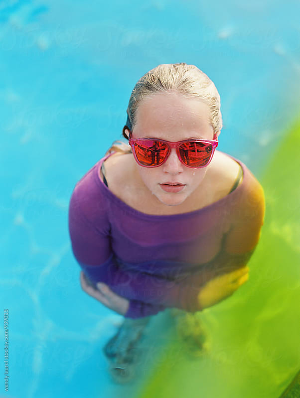 girl in pink sunglasses with yellow and green in pool by wendy laurel for Stocksy United