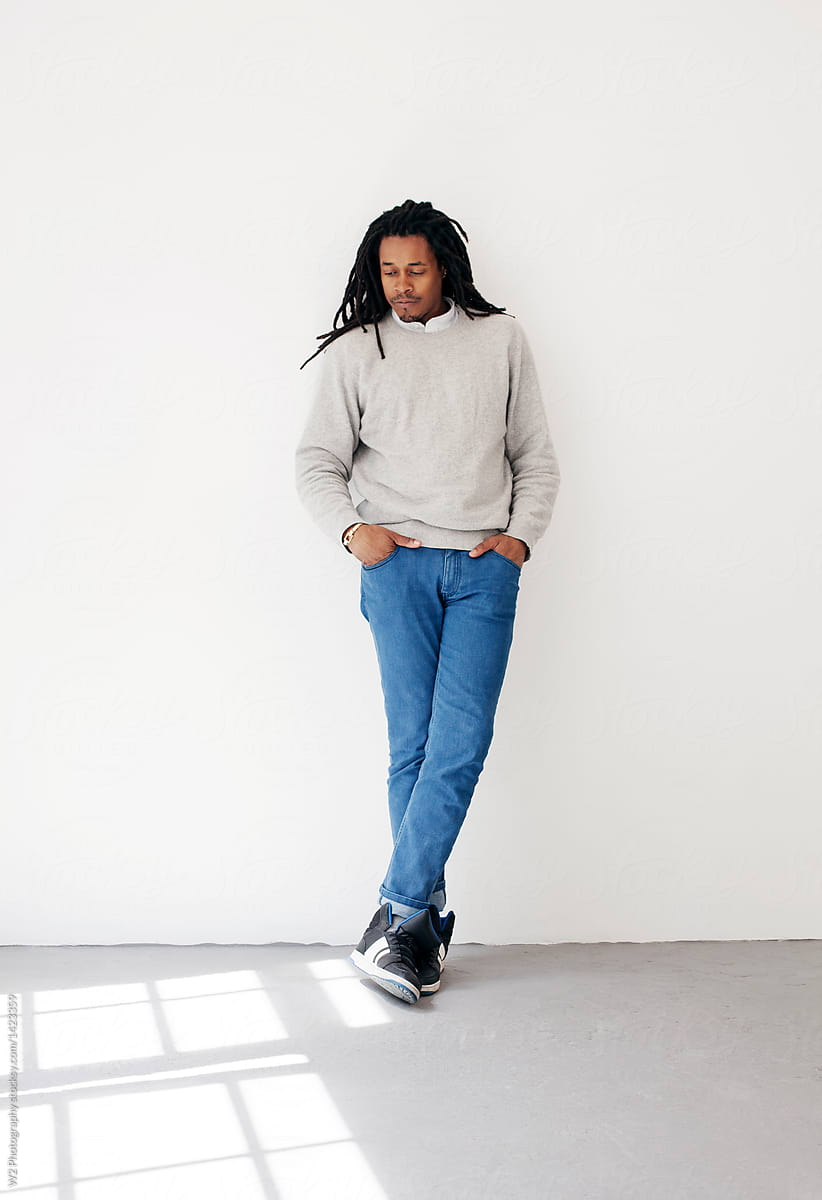 Full Body Portrait Of Black Man Leaning Against A Wall By