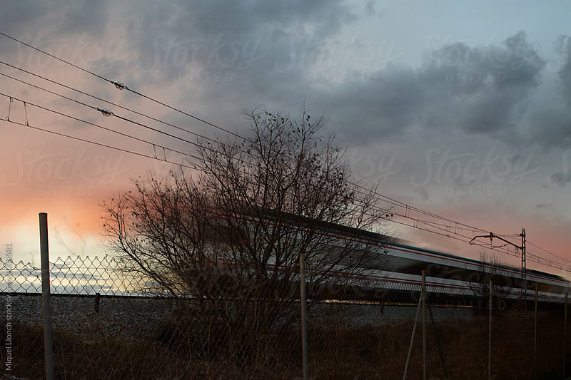 Railway train in motion at sunset by Miquel Llonch for Stocksy United