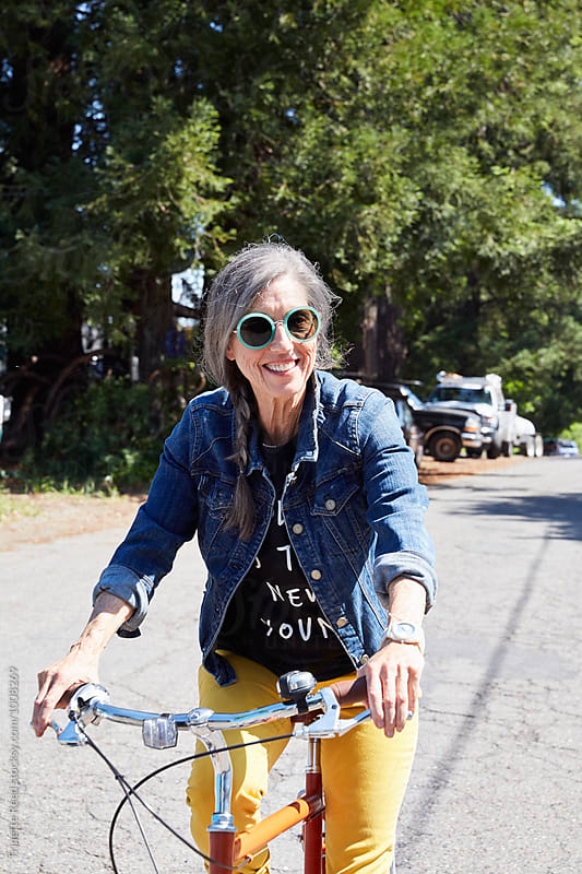 Portrait of stylish senior woman riding a bike outdoors by Trinette Reed for Stocksy United