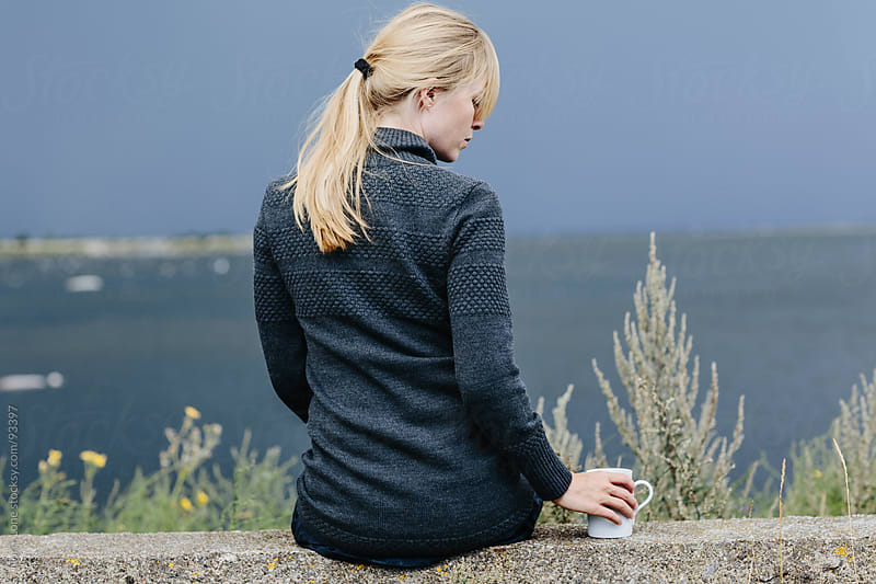 Woman drinking coffee by the sea by Lior + Lone for Stocksy United