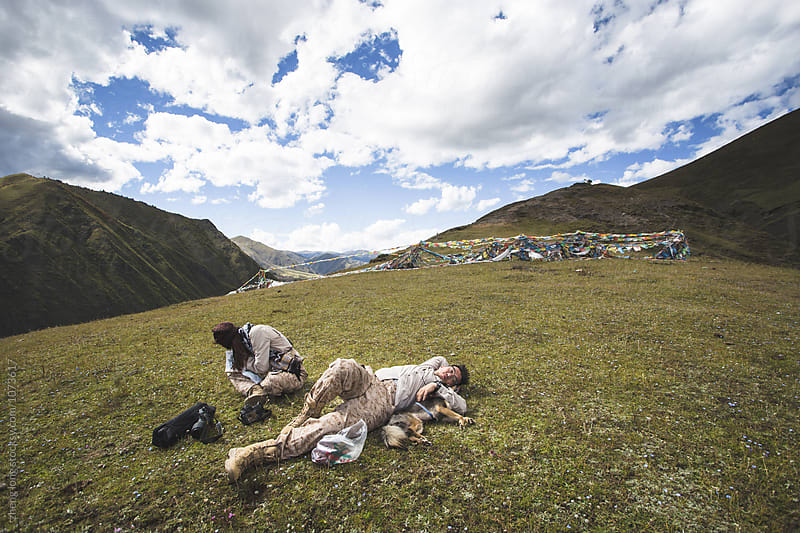 young couple relax on the grass land by zheng long for Stocksy United