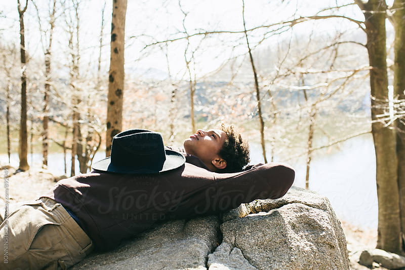 Mountaineer in the woods resting on rock. by BONNINSTUDIO for Stocksy United