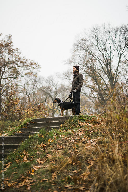 A man and his dog on a walk by Isaiah & Taylor Photography for Stocksy United