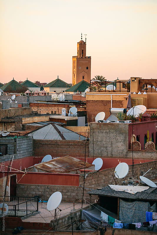 Cityscape and rooftops with minaret tower of a mosque at sunset by Alejandro Moreno de Carlos for Stocksy United