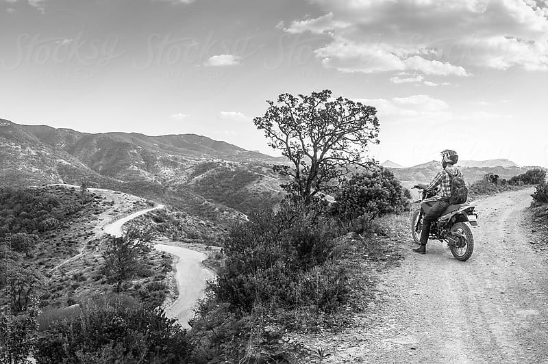 Motorbike rider enjoying a vast mountain scenery by Per Swantesson for Stocksy United