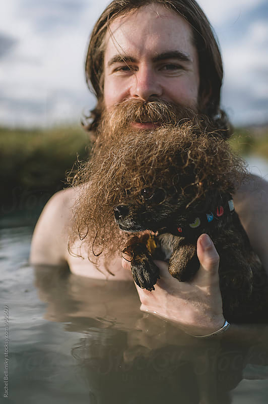 A handsome bearded man with his dogs in beautiful desert hot springs during the golden hour by Rachel Bellinsky for Stocksy United