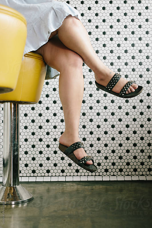 Women's feet; Woman sits on yellow stool by Simone Anne for Stocksy United