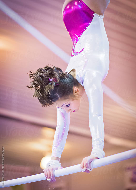 Female Gymnastis Performing Bars Routine by Brian McEntire for Stocksy United