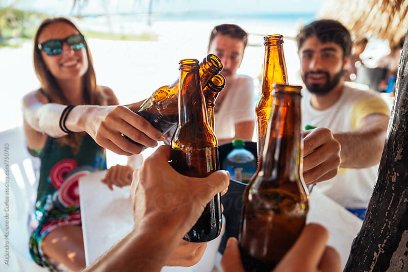 Friends toasting their bottles of beer in a beach bar by Alejandro Moreno de Carlos for Stocksy United
