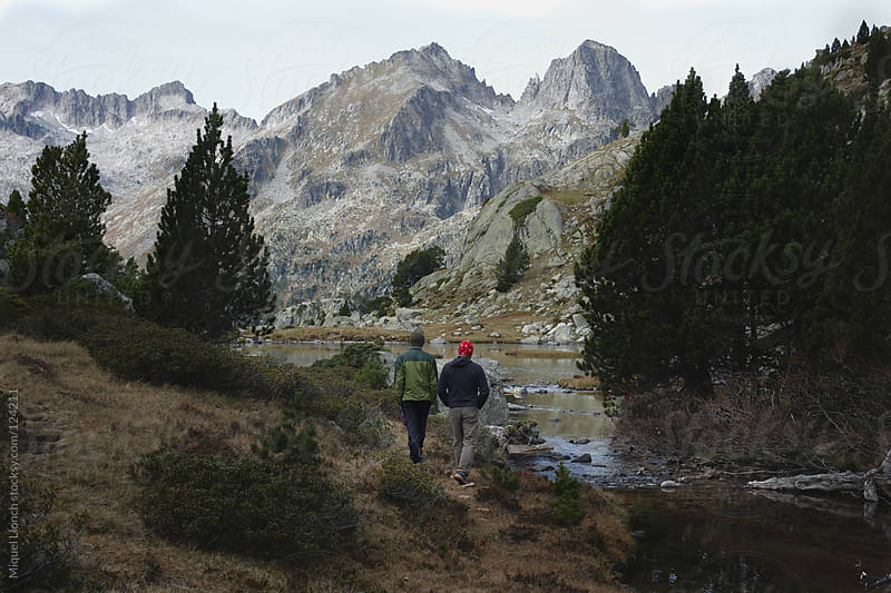 Two men hiking by the mountains and a lake in the Pyrenees by Miquel Llonch for Stocksy United