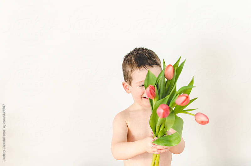 Little boy holding a bunch of tulips by Lindsay Crandall for Stocksy United