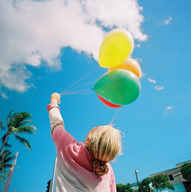 girl against bright blue sky with rainbow bunch of balloons by wendy laurel for Stocksy United