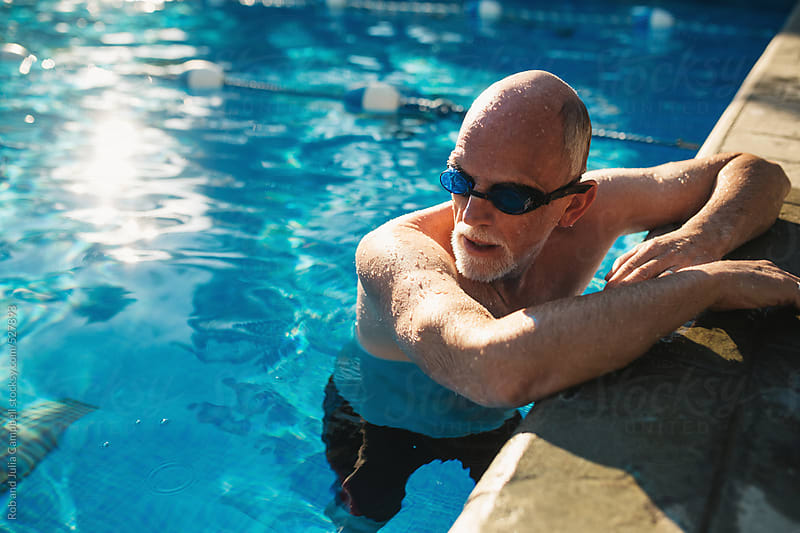 Active older man working out in outdoor swimming pool by Rob and Julia Campbell for Stocksy United
