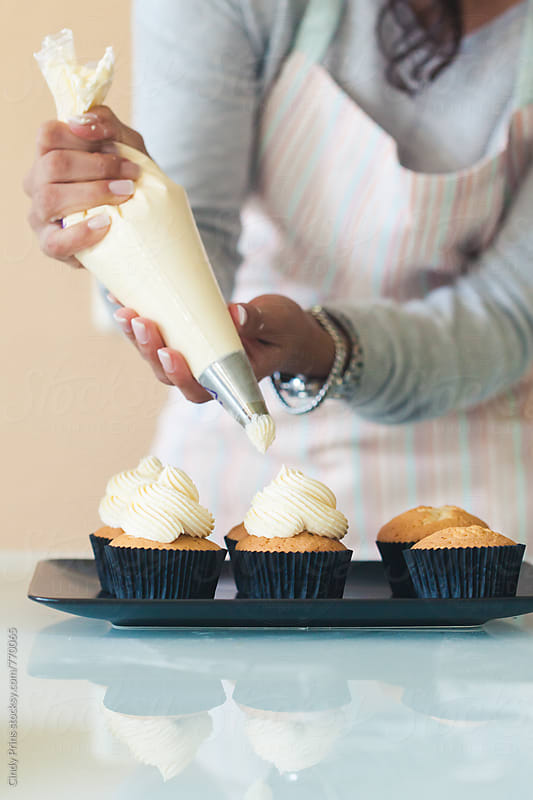 Woman putting vanilla frosting on cupcakes by Cindy Prins for Stocksy United