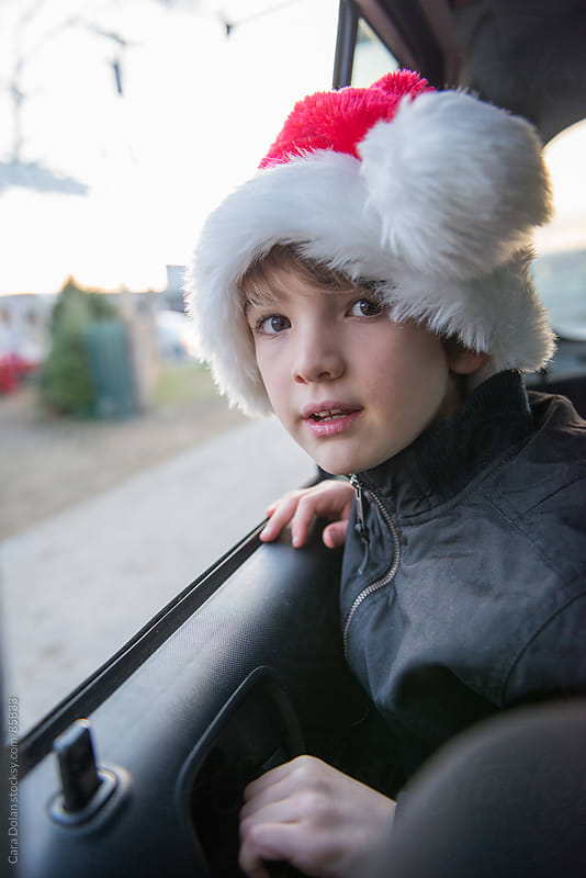 Boy in Santa hat leans out the car wintow as his family arrives at a Christmas tree stand by Cara Dolan for Stocksy United