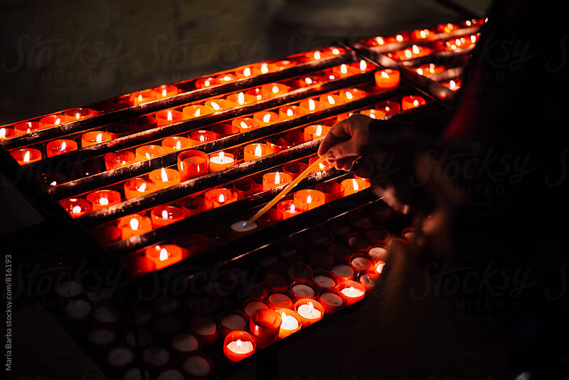 Lighting candles inside of a church. by María Barba for Stocksy United